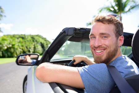 young adult man: Driving car man happy on road trip travel holidays. Portrait of a young adult smiling at camera ready for his vacations with his new convertible purchase or leasing.
