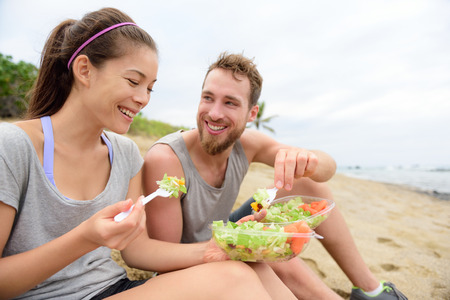 âhealthy: Gente joven feliz comiendo ensalada saludable para el almuerzo. Grupo multirracial que tiene una rotura en los bocadillos de playa en una comida para llevar vegano de verduras verdes y zanahorias riendo juntos. Estilo de vida casual.