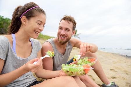Jeunes heureux de manger une salade saine pour le déjeuner. Groupe multi-ethnique ayant une pause sur la plage de snacking sur un repas à emporter végétalien de légumes verts et les carottes de rire ensemble. Style de vie décontracté. Banque d'images