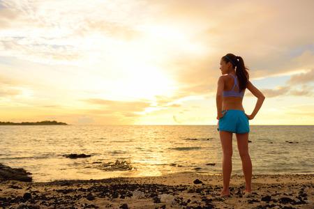 Aspiration - femme regarde au loin avec l'inspiration. Fitness femme après course dans le coucher du soleil sur la plage en regardant l'océan sentiment paisible et sereine de détente pendant l'été. Concept de la pleine conscience. Banque d'images