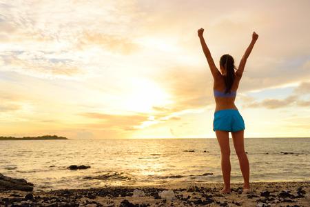La libertad mujer ganadora animando en la playa de la puesta del sol. Concepto del éxito con la hembra adulta de los brazos de nuevo hacia el cielo buscando en el océano sentirse libre y exitosa. El logro de su vida. Foto de archivo
