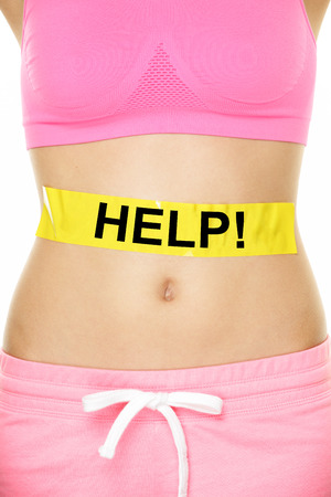 self conscious: Stomach help concept - woman with body weight problem. Closeup of waist of female adult showing yellow label on abdomen with word HELP written for digestion, health, reproduction or diet issues. Stock Photo