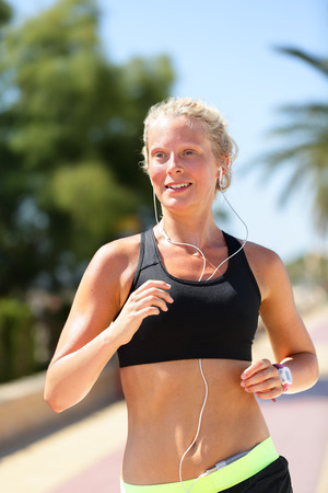 Female runner running listening smartphone music. Blonde woman exercising her cardio jogging in the city wearing a black sports bra and a smartwatch activity tracker listening music with earphones. photo
