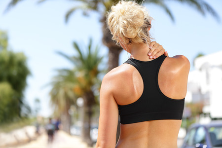 Neck pain during training. Athlete running Caucasian blond woman runner with sport injury in sports bra rubbing and touching upper back muscles outside after exercise workout in summer.