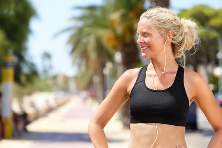 escucha activa: Fitness mujer activa en el deporte sujetador y auriculares escuchando m�sica. Corredora bastante rubia mira a la cara feliz y motivado antes de ir a correr y correr en la ciudad en un d�a de verano.