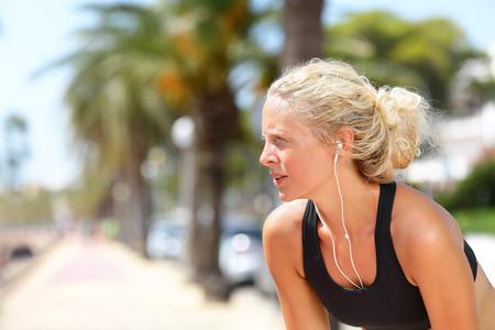 Moe lopende vrouw nemen van een pauze tijdens uitvoeren. Mooi jong blond atletische vrouwelijke volwassen rusten haar adem vangen tijdens het joggen en luisteren naar muziek met een koptelefoon en smartphone app.