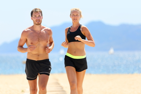 Fitness running couple exercising cardio on beach. Attractive sexy fit young adults jogging together during summer day sweating under the sun wearing black shorts and sports bra. Weight loss concept. photo