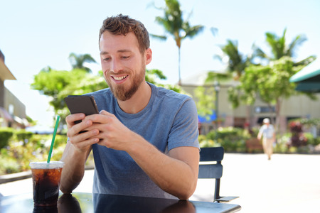 Man on cafe using smart phone app text messaging sms drinking iced coffee in summer. Handsome young casual man using smartphone smiling happy sitting outdoors. Urban male in his 20s. Stock Photo