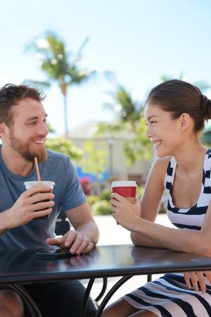Cafe couple having fun drinking coffee talking smiling and laughing on date in summer. Young man talking with Asian woman sitting outdoors. Happy friends in late 20s. photo