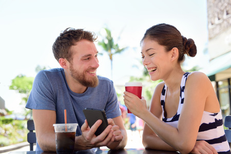laughing: Couple on cafe looking at smart phone app pictures drinking coffee in summer. Young urban man using smartphone smiling happy to casual asian woman sitting outdoors. Friends in late 20s