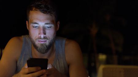 소셜 미디어를 업데이트 밤 인터넷 검색에서 스마트 폰을 사용하는 사람 (남자). 여름에 어둠 속에서 야외 휴대 스마트 폰을 사용하여 수염을 가진 젊