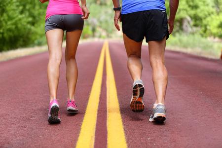 Lopende mensen. Lopers joggen close-up van sport fitness loopschoenen en benen en korte broek. Atleten, vrouw en man in de buitenlucht workout training voor de gezondheid en fitness.