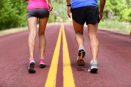 people together: Running people. Runners jogging close up of sport fitness running shoes and legs and shorts. Athletes, woman and man in outdoor workout training for health and fitness.