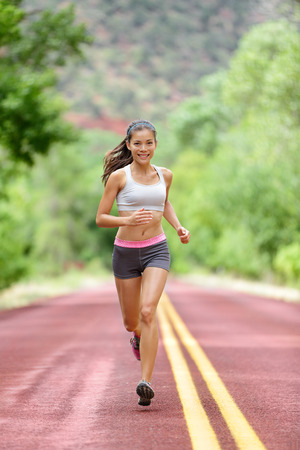 Runner woman running training living healthy fitness sport lifestyle. Active female athlete jogging outdoors happy with aspirations. Beautiful mixed race Asian Caucasian girl in full body length. Stock Photo