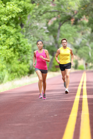 intensity: People running on road. Sport and fitness runners woman and man training for marathon run doing high intensity interval training sprint workout outdoors. Athletes sports models fit and healthy.