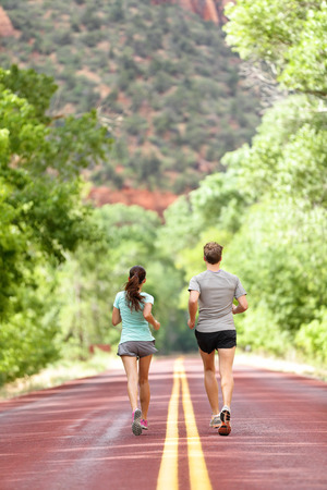 Runners running on road in nature away from camera. Couple, woman and man jogging for a run outside in amazing mountain landscape. Full body length rear view of back. Fitness and healthy lifestyle.