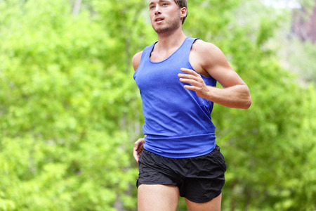 Hombre que se ejecuta en la carretera. Deporte y fitness entrenamiento del corredor de maratón haciendo entrenamiento de alta intensidad intervalo de entrenamiento de sprint al aire libre en verano. Hombre ajuste atleta modelo deportivo y aspiraciones saludables.