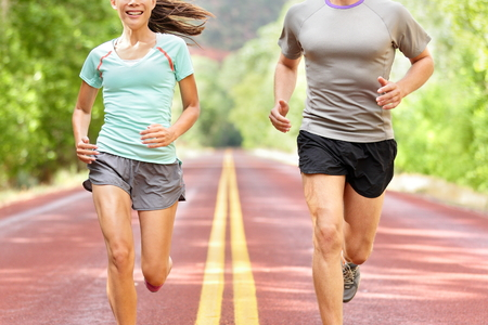 Gesundheit und Fitness Lauf. Läufer auf Lauftraining während Fitnesstraining draußen auf der Straße. Menschen Joggen Zusammenleben gesunden aktiven Lebensstil im Sommer draußen. Mittlerer Teil von Frau und Mann.