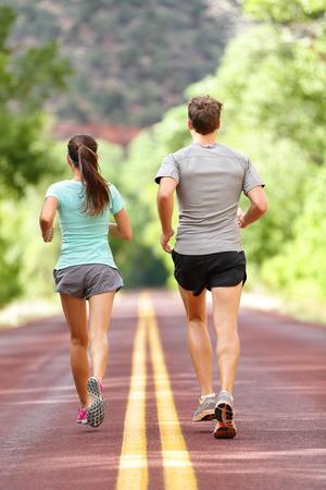 Runners course et le jogging pour la santé et la forme physique. Les gens sur la condition physique courent sur la route dans la nature. Couple, la femme et de la formation de l'homme à l'extérieur pour le fitness et la vie saine. La pleine longueur du corps de la vue arrière du dos.