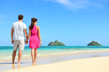 Beach summer holiday - couple on Hawaii beach vacation standing in white sand relaxing looking at ocean. Romantic young adults holding hands on Lanikai beach, Oahu, Hawaii, USA with Mokulua Islands.