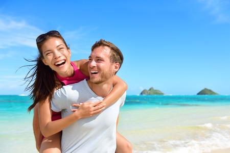 hawaii: Beach couple having fun laughing on Hawaii holiday. Beautiful Asian mixed race woman piggybacking on Caucasian boyfriend on Lanikai beach, Oahu, Hawaii, USA with Mokulua Islands.