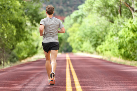 behind: Male runner running on road training for fitness. Man doing jogging workout run outside in summer in nature. Athlete in running shoes and shorts working out for marathon.