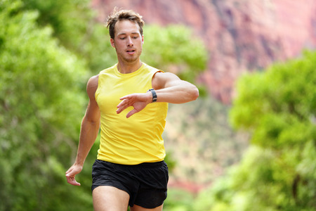 heart rate monitor: Runner looking at heart rate monitor smartwatch while running. Man jogging outside looking at his sports smart watch during workout training for marathon run. Fit male fitness model in his 20s.