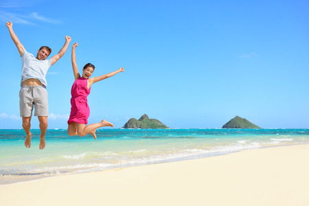 Hawaii beach Vacation. Happy couple tourists jumping. Young couple cheering for summer holidays showing success, happiness, and joy on Lanikai beach, Oahu, Hawaii, USA with Mokulua Islands. Stock Photo