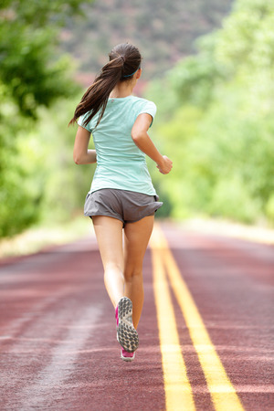 out of body: Young lady working out running away on rural road. Woman runner athlete training jogging during workout outside. Full body length rear view showing back. Girl in shorts and running shoes.