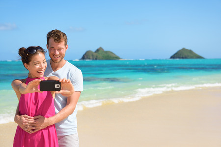 Beach vacation couple taking selfie photograph using smartphone, Lanikai beach, Oahu, Hawaii, USA with Mokulua Islands. Couple holding smart phone camera. Young beautiful multicultural Asian Caucasian 版權商用圖片
