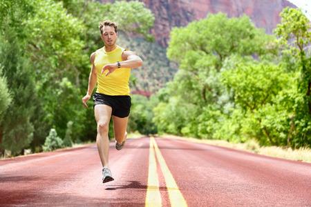 corriendo: Hombre corriente sprint mirando monitor de frecuencia card�aca SmartWatch en ejecuci�n. Hombre que activa fuera mirando a sus deportes de relojes inteligentes durante el entrenamiento del entrenamiento para el marat�n. Ajuste del modelo masculino de la aptitud de unos 20 a�os.