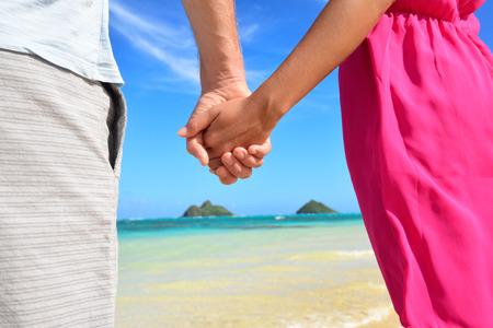 Beach couple in love holding hands on honeymoon. Pink dress, casual beachwear romantic newlyweds people standing on travel summer vacations on Lanikai beach, Oahu, Hawaii, USA with Na Mokulua Islands. photo