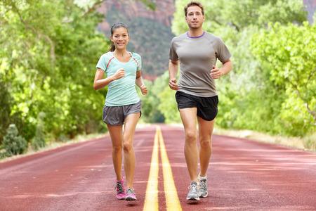 Hardlopen Gezondheid en fitness. Agenten op run training tijdens fitness workout buiten op de weg. Mensen joggen samenleven gezonde actieve leefstijl buiten in de zomer. Full body lengte van de vrouw en man Stockfoto