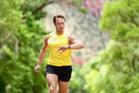 Running looking at heart rate monitor smartwatch while running. Male runner jogging outside looking at sports smart watch during workout training for marathon run. Fit male fitness model in his 20s. Stockfoto
