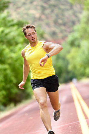heart monitor: Runner looking at heart rate monitor smart watch while running. Man jogging outside looking at his sports smartwatch during workout training for marathon run. Fit male fitness model in his 20s.