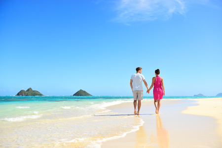 여행: Beach honeymoon couple holding hands walking on white sand beach. Newlyweds happy in love relaxing on summer holidays on Lanikai beach, Oahu, Hawaii, USA with Mokulua Islands. Travel vacation concept.
