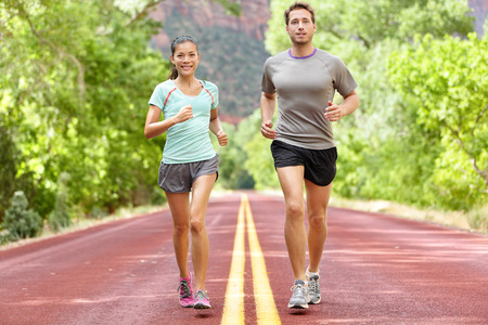 sports training: Running Health and fitness. Runners on run training during fitness workout outside on road. People jogging together living healthy active lifestyle outside in summer. Full body length of woman and man