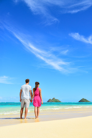 Beach vacation couple relaxing on summer holidays. Young people standing from behind holding hands looking at the ocean on Lanikai beach, Oahu, Hawaii, USA with Na Mokulua Islands. 版權商用圖片