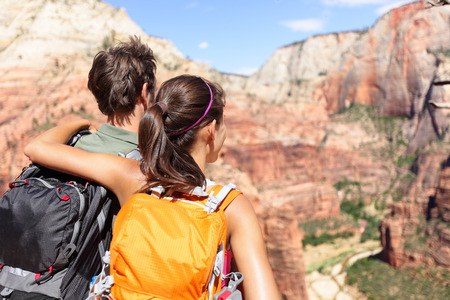 hiking: Hiking - hikers looking at view in Zion National park. People living healthy active lifestyle dong hike in beautiful nature landscape to Observation Point near Angles Landing, Zion Canyon, Utah, USA. Stock Photo