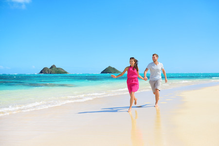 ビーチ ハワイ楽しんで実行している幸せなカップル。ロマンチックなカップルは喜びと幸福に満ちては、ラニカイビーチ、モクルア島とオアフ島、 写真素材