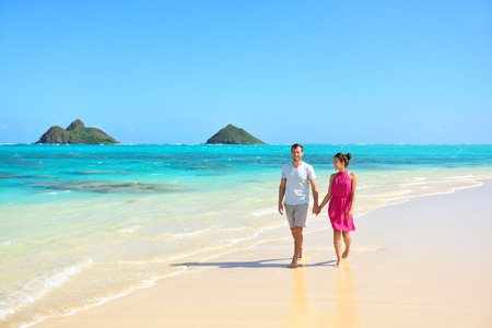 hawaii islands: Summer vacation couple walking on beach landscape. Young adults relaxing together enjoying their holidays by pristine turquoise water on Lanikai beach, Oahu, Hawaii, USA with Mokulua Islands.