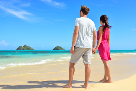 Beach couple looking at ocean view from behind. Couple standing on white sand in pink dress and beachwear on vacations on Lanikai beach, Oahu, Hawaii, USA with Na Mokulua Islands.