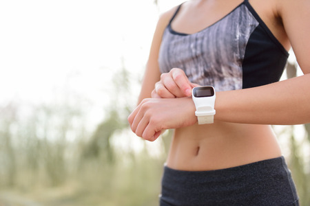 Smart watch for sport. Athlete wearing heart rate monitor. Runner looking at sports smartwatch going running outside. Female athlete tracking her activities using wearable technology. Banco de Imagens
