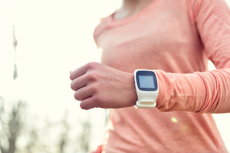 workout: Heart rate monitor smart watch for sport. Athlete wearing heart rate monitor. Runner using sports smartwatch on running workout outside. Female athlete tracking activities using wearable technology.