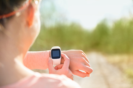 Smart watch for sport. Athlete wearing heart rate monitor. Runner looking at sports smartwatch going running outside. Female athlete tracking her activities using wearable technology. Stock Photo