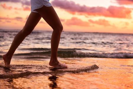 woman barefoot: Running woman jogging barefoot in water at beach sunset. Close up of female feet of runner splashing in the edge of water. Girl training alone.