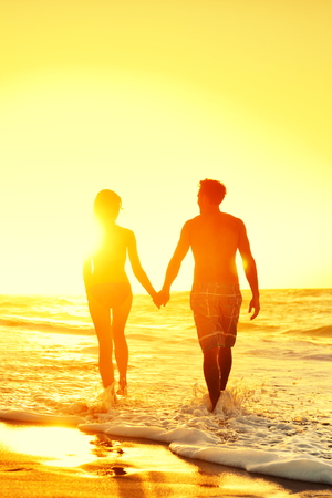 bikini couple: Beach honeymoon couple romantic in love holding hands at beach sunset. Newlywed happy young couple enjoying ocean sunset during travel holidays vacation getaway. Stock Photo