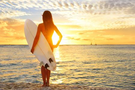 Surfa surfare flicka tittar på Ocean Beach solnedgången. Silhouette kvinnliga bikini kvinna tittar på vatten med stående med surfbräda ha roligt leva hälsosamt aktiv livsstil. Vattensporter med modell. Stockfoto