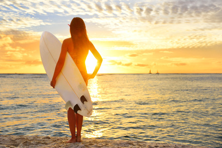 Surfing surfer girl looking at ocean beach sunset. Silhouette of female bikini woman looking at water with standing with surfboard having fun living healthy active lifestyle. Water sports with model. Stock Photo