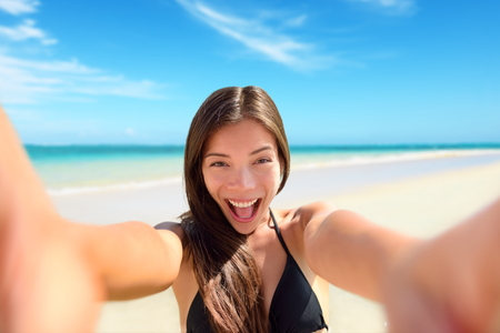 excited: Selfie fun woman taking photo at beach vacation. Summer holiday girl happy at smartphone camera taking self-portrait on her travel vacations on pristine paradise beach.